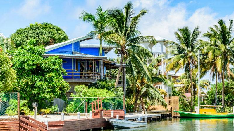 blue house in Belize, in front of a dock with boats on a lake